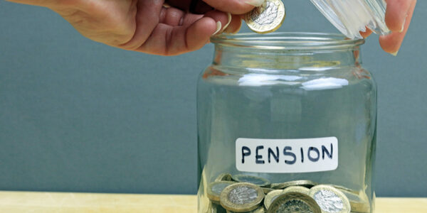 Pound being dropped into jar labelled pension